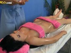 Sweet brunette is fingerbanged on the massage table
